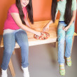 Two pretty girl with pizza on desk — Stok fotoğraf