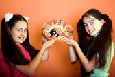 Two young girls show on pizza — Stok fotoğraf
