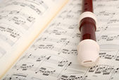 Flute on musical sheet — Stock Photo