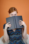 Woman hides the face behind the book — Stock Photo