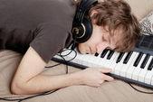Man asleep on the MIDI-keyboard — Stock Photo