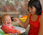 Mother feeds the little daughter — Stock Photo
