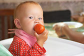 Kid eats a tomato — Stock Photo