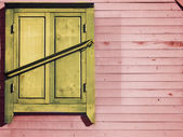 Vintage wooden wall with a locked window — Stock Photo