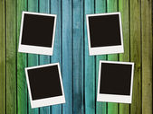 Four blank photos on wooden wall — Stockfoto