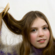 Portrait of the young girl combing hair — Stock Photo