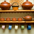 Ceramic utensils on a wooden shelf - Stock Photo