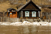 Old house on coast of the spread river — Stock Photo