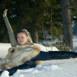 Young girl laying on snow in wood. - Stock Photo