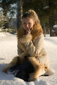 Young girl sitting on snow in wood. — Stock Photo