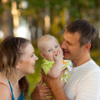 Young happy family in wood — Stock fotografie