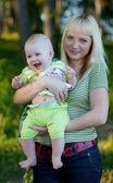 Mamma och skrattande barn natur — Stockfoto
