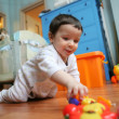 Infant plays on floor, soft focus — Stock Photo