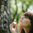Girl blows soap bubbles — Stock Photo
