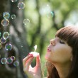 Girl blows soap bubbles — Stockfoto
