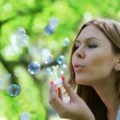Royalty-Free Stock Photo: Young woman blows soap bubbles