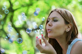 Young woman blows soap bubbles — Stock Photo