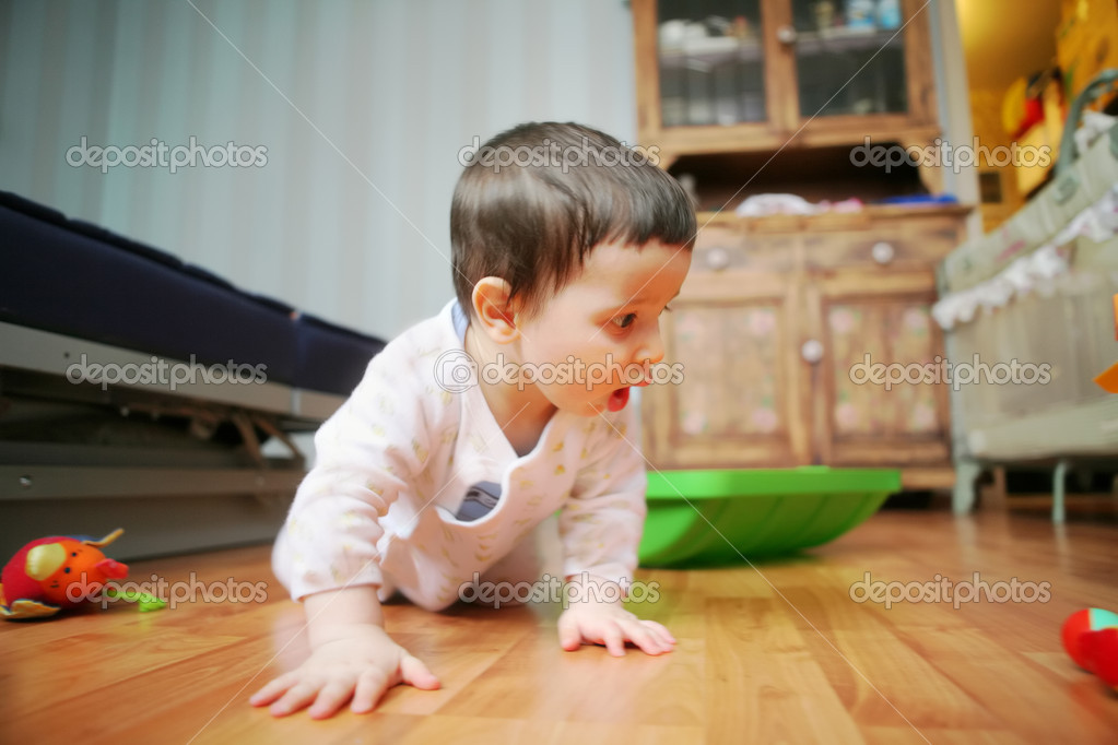 Adorable infant plays on floor in the room with furniture, soft focus — Stock Photo #1187196