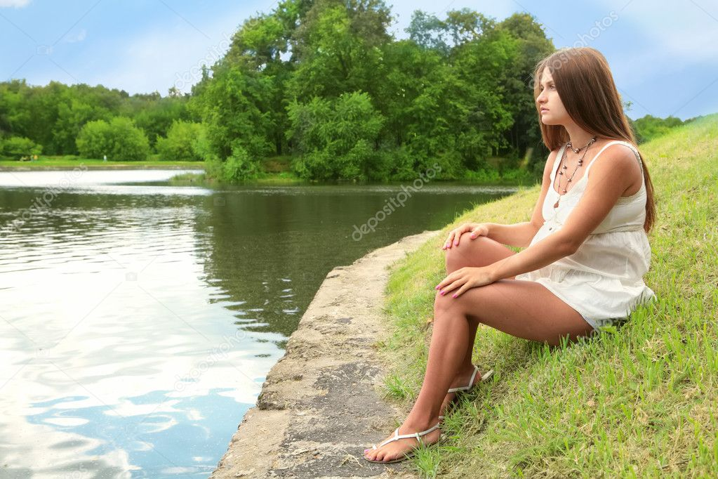 Pregnant woman sits on herb near lake — Stock Photo #1187219