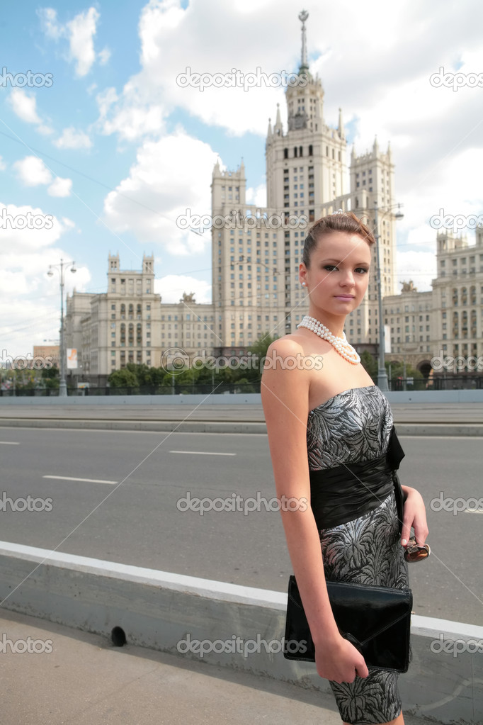 Beautiful girl in black-silvery dress on background of the old moscow skyscraper — Stock Photo #1188081