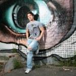 Lad near wall with graffiti — Stock Photo