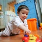 Infant plays on floor, soft focus — Stock Photo
