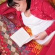 Stock Photo: Expectant mother reads book