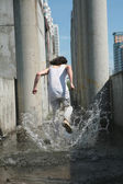 Man in white cloth runs away on water amongst concrete construction — Stock Photo