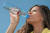 Black african girl drinks a water — Stock Photo