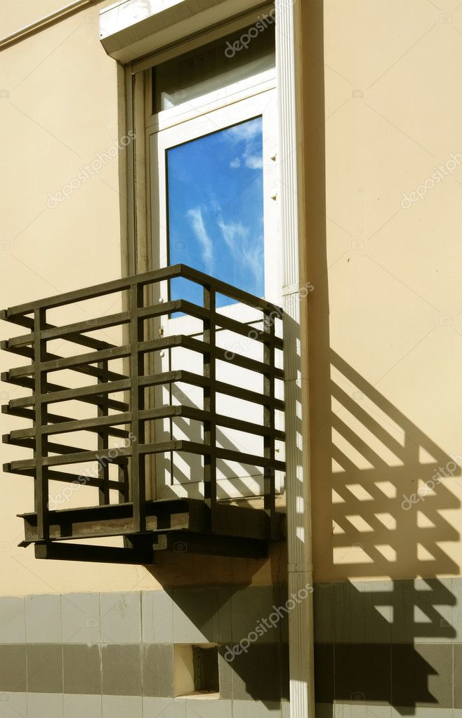 Metallic balcony, his shade on yellow wall and blanching door with reflection blue sky  Stock Photo #1373782