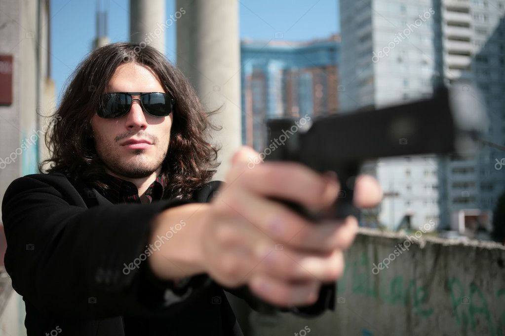 Young man with gun in image of the killer in style of the italian film about mafia — Stock Photo #1375118