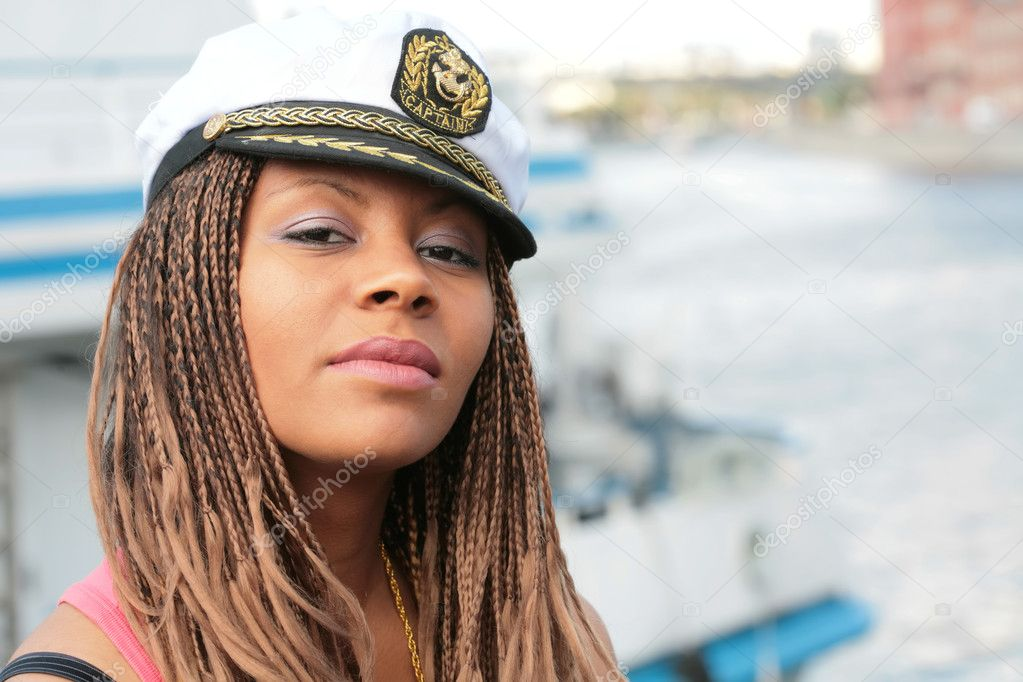 Girl in captain cap on background of the motor yacht  Stock Photo #1375487