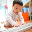 Baby and computer keyboard, soft focus — Stock Photo