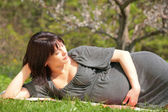 Pregnant woman in blossom garden — Stock Photo