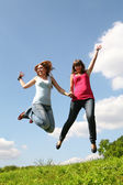 Two girls jump under blue sky — Stock Photo