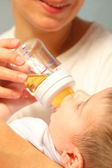 Child eats from bottle — Stock Photo