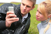 Guy and girl look at device — Stock Photo