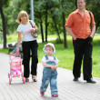 Family on walk in summer park — Stock Photo
