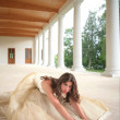 Bride in golden gown on floor — Stock Photo