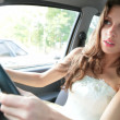 Young woman drives a car - Stock Photo