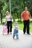 Family on walk in summer park — Stok fotoğraf