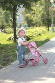 Little girl walks with toy sidercar — Stock Photo