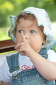 Small girl with finger near face — Stock Photo