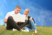 Young man and girl blonde with laptop — Stok fotoğraf