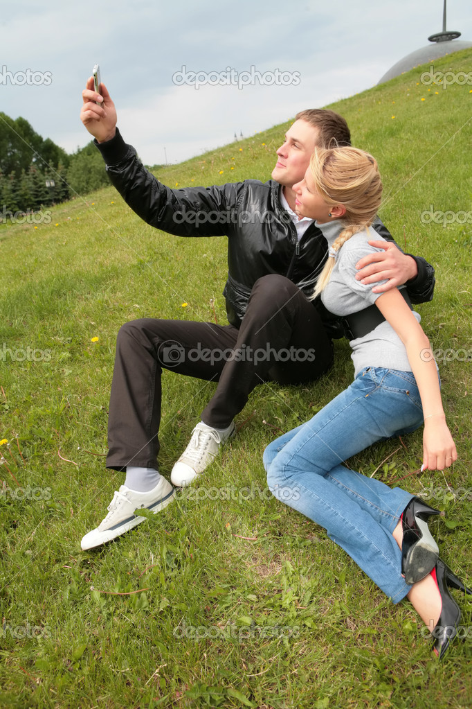 Gay in black jacket shows device to blond girl — Stock Photo #1410146