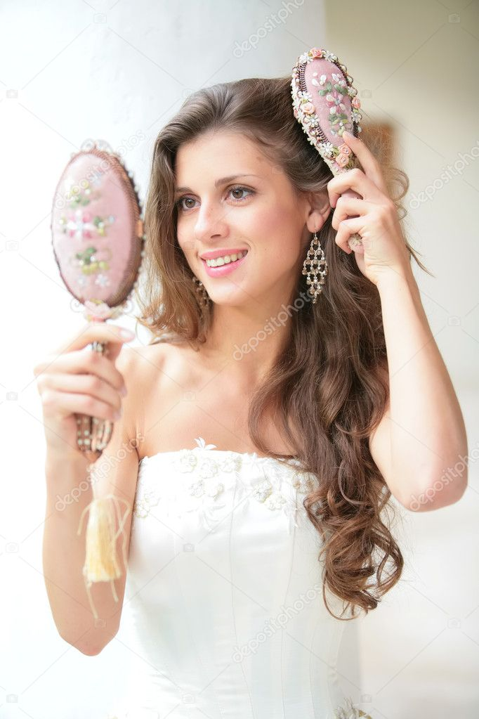 Smiling beautiful girl does combs hair old-time comb  Stock Photo #1414501
