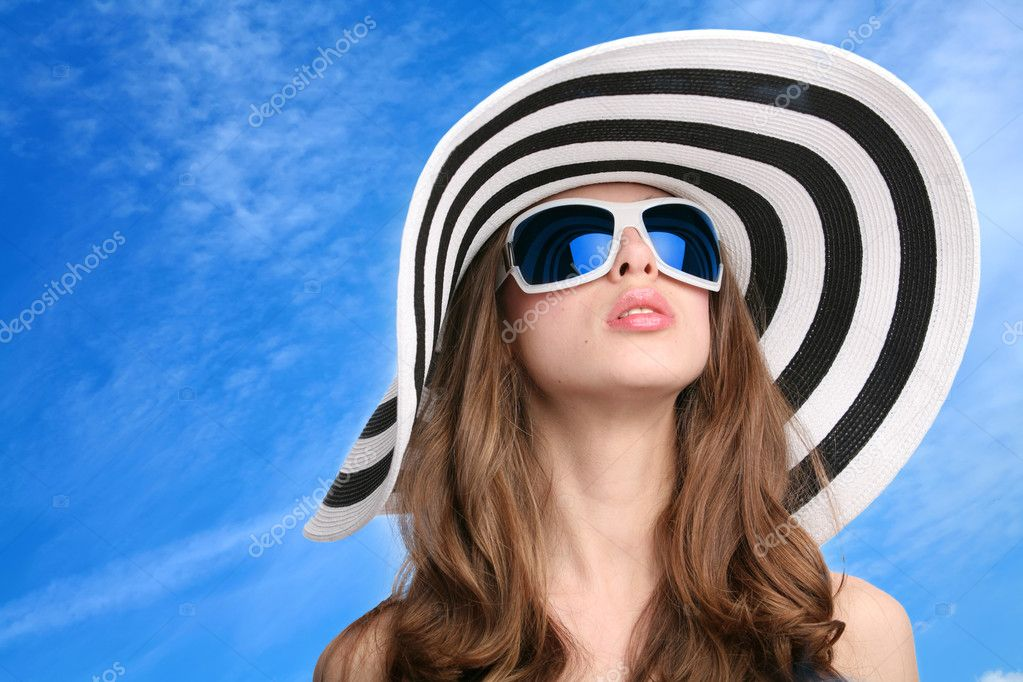 Beautiful girl in striped hat and sunglasses on background blue sky — Stock Photo #1415863