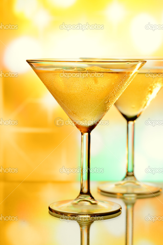Cocktail glasses with ice and holiday lights in the background — Stock Photo #1189200