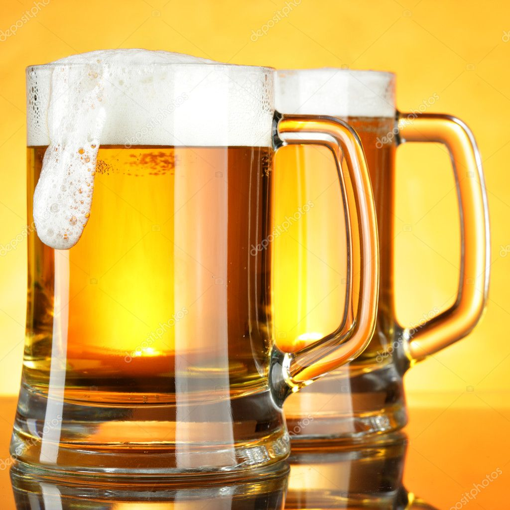 Beer mugs with froth over yellow background — Stock Photo #1192280
