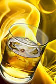 Glass of whisky with ice and fire in the background — Stock Photo